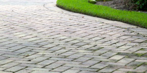 Low angle view of  light colored rectangular brick pavers in alternating pattern edged with grass.